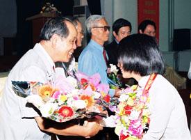 Sinh viên mới nhập trường tặng hoa PGS.TS Bùi Hiền
